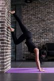 Beginning female yogi practicing yoga inversion poses standing on hands upside down leaning against wall in fitness club Stock Images