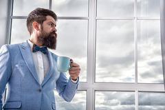 Beginning of great day. Important day in his life. Get ready. Enjoy every minute. Hipster in tuxedo with bow tie making. Sip of coffee. But first coffee. Man stock photo
