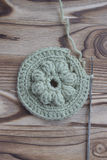 The beginning of handmade crocheted cotton organic doily, coaster or napkin, on wooden background. Metal crocheting hook Royalty Free Stock Photography