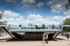 Beginning of the Millennium Bridge. LONDON, UK - JUNE 11, 2014: Tourists walk past the Southbank end of the Millennium Bridge stock photography