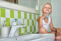 Boy brushing teeth in the bathroom.The beginning of a new day royalty free stock images