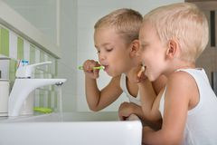 Two brothers brush my teeth in the bathroom.The beginning of a new day. The beginning of a new day.Two brothers brush my teeth in the bathroom royalty free stock photos