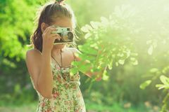 Beginning photographer. A little girl takes pictures of a tree on her film photo camera Royalty Free Stock Images