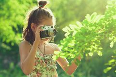 Beginning photographer. A little girl takes pictures of a tree on her film photo camera Stock Photography