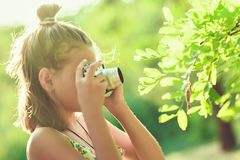 Beginning photographer. A little girl takes pictures of a tree o Royalty Free Stock Photography