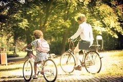 Beginning of the school. African American father and daughter driving bike trough park royalty free stock photo