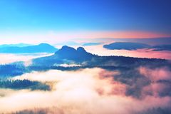 Beginning of spring. Fantastic dreamy sunrise above deep valley hidden in the rocky mountains . Spring misty day Royalty Free Stock Images