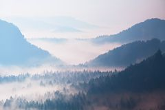 Beginning of spring. Fantastic dreamy sunrise above deep valley hidden in the rocky mountains . Spring misty day Stock Image
