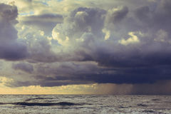 Beginning of the storm rain in ocean, dark cloudy sky Stock Photography