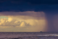 Beginning of the storm rain in ocean, dark cloudy sky Royalty Free Stock Photo