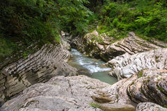 Beginning of stormy mountain river among smooth light beige walls of the canyon Royalty Free Stock Photo