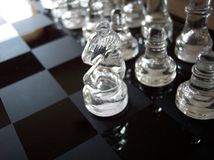 Beginning of a Strategy. A knight makes the first move forth on the glass chessboard Royalty Free Stock Images