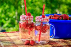 Summer refreshing drink homemade lemonade with strawberries in glasses with a straw stock photography