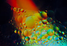 Beginning of Time and Space. A depiction of space and time using oil on water macro. Looks like the beginning of time and space with planets evolving in the Stock Image