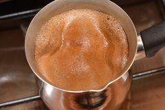 The beginning to boil coffee in the Turk on a plate, the top view stock image