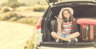 Little cute girl in the trunk of a car with suitcases stock photography