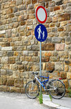 Beginning of Walk Area. Parked bicycle and signs on the pole to indicate beginning of walk area in Prague, Czechia in the stone wall background Royalty Free Stock Image