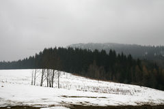 Beginning of winter. Peak Szczeliniec Wielki in Mountains Table, Poland  in misty, gloomy winter day. Pasterka village in Poland. Beginning of winter Royalty Free Stock Photography