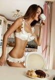 Begint het ochtend jonge mooie meisje met een kop van koffie en smakelijke koekjes met chocolade Royalty-vrije Stock Foto