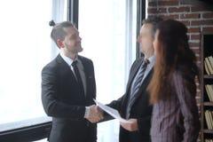Begleiter des Händedrucks zwei bei einer Sitzung im Büro stockbild