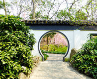 Begonia flowers blooming. Through a round door to appreciate Malus spectabilis inside Guilin Park early spring in Shanghai China Royalty Free Stock Images