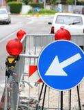 Begränsa av körbanan med röda signallampor och ett vägmärke t royaltyfria foton