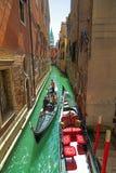 Begränsa den Venetian kanalen med gondoljären och turister i gondolen Fotografering för Bildbyråer