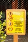 Begränsande tecken för klänningkod på en restaurang bredvid en pöl och en strand (lodlinjen) Fotografering för Bildbyråer