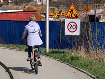 Begränsning av trafik till km/tim 20 nära konstruktionsplatsen En kvinna på en cykel kör längs trottoaren nära tankeskapelsen Royaltyfri Bild