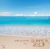 Begrüßen Sie zum Sommer 2017, der auf einen tropischen Strand geschrieben wird Lizenzfreie Stockfotos