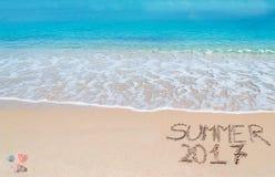 Begrüßen Sie zum Sommer 2017, der auf einen tropischen Strand geschrieben wird Stockbild
