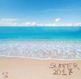 Begrüßen Sie zum Sommer 2017, der auf einen tropischen Strand geschrieben wird Lizenzfreie Stockbilder