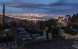 Begraafplaats in nicht met het verlichte oude stadspanorama van stock afbeeldingen