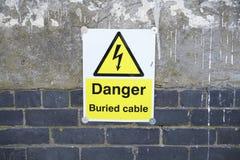 Begrabene Gefahr des elektrischen Kabels auf Wand lizenzfreies stockfoto