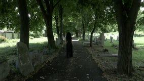 Begrafenis gotische weduwenvrouw in zwarte die kroon het in hand lopen in oude begraafplaatssteeg houden stock video