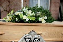 Begrafenisbloemen op een kist stock foto's
