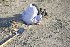 Begrava ditt huvud i sanden arkivfoto