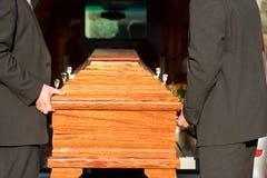 Begravning med casketen som bärs av kistabäraren arkivbild