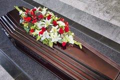 Begravning som dekoreras beautifully med kistan för blommaordningar arkivfoton