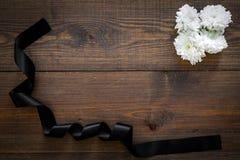 Begravnings- symboler Vit blomma nära svart band på mörkt träutrymme för bästa sikt för bakgrund för text arkivbilder