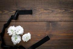 Begravnings- symboler Vit blomma nära svart band på mörkt träutrymme för kopia för bästa sikt för bakgrund arkivfoto