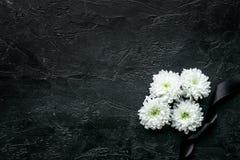 Begravnings- symboler Vit blomma nära svart band på svart utrymme för bästa sikt för bakgrund för text arkivbild