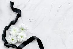 Begravnings- symboler Vit blomma nära svart band på vitt utrymme för bästa sikt för stenbakgrund för text arkivbild