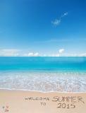 Begrüßen Sie zum Sommer 2015, der auf einen tropischen Strand geschrieben wird Stockbilder