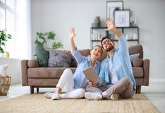 Begrepp av att flytta sig, köpande hem gift parplan som reparerar och som projekterar lägenheten royaltyfri fotografi