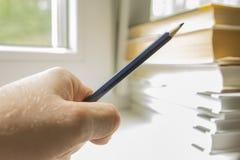 Begrepp av att lära, blyertspenna i hand med böcker Arkivbild