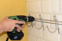 Begrepp av att omdana f?r badrum installation av h?ngare, handdukh?llare med en skruvmejsel arbetarh?ngningar en h?ngare, krokar  royaltyfri bild