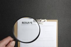 Begrepp av att välja den yrkesmässiga kandidaten för ett jobb Hand som rymmer en förstoringsapparat och granskar meritförteckning royaltyfria foton
