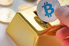Begrepp av Cryptocurrency fysisk bitcoin med spargrisen för guld- guldtacka royaltyfri foto