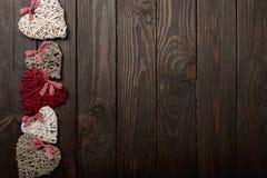Begrepp av dagen för valentin` s Vide- hjärtor på mörk träbackgro Arkivfoto